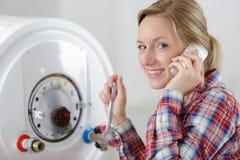 Plumber woman builder fixing boiler. Woman stock photos