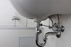 Plumber work. Sewage pipe of a  Sink in a modern bath room Royalty Free Stock Photography