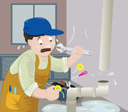 Plumber at work. A plumber working hard trying to fix a leaking pipe Stock Photo
