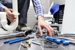 Plumber at work in a bathroom, plumbing repair service, assemble. And install concept stock photo