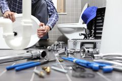 Plumber at work in a bathroom, plumbing repair service, assemble Royalty Free Stock Photos