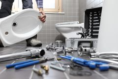 Plumber at work in a bathroom, plumbing repair service, assemble Stock Images