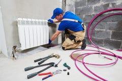 Plumber at work. Installing water heating radiator stock image