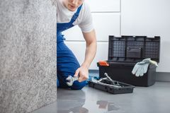 Plumber during work. Plumber holding a wrench, working on a leak in the kitchen stock photography