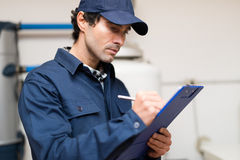 Plumber at work writing on a clipboard Royalty Free Stock Photos