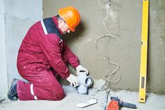 Plumber worker installing sewage pipes in sewerage system Royalty Free Stock Images