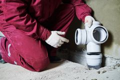 Plumber worker installing sewage pipes in sewerage system Stock Photo