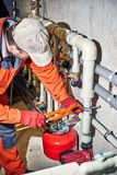 Repair of hydraulic heating system in the house. Plumber worker repairs the heating system in the house royalty free stock photo