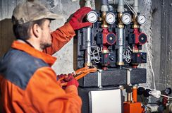 Repair of hydraulic heating system in the house. Plumber worker repairs the heating system in the house royalty free stock images