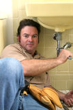 Plumber Working. A plumber using a wrench to tighten a pipe under a sink Stock Photo
