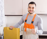 Plumber working at home of client Royalty Free Stock Image