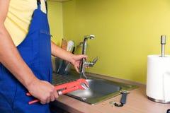 Plumber working in kitchen, repairing faucet royalty free stock photo