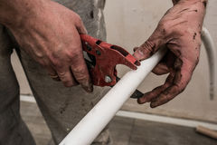 Plumber working man cuts urgently dirty hands white pipe to repa Stock Image
