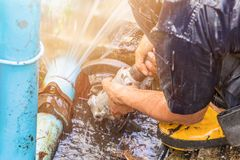 Plumber working repair the broken pipe and replace in hole with water Motion at roadside.  royalty free stock image