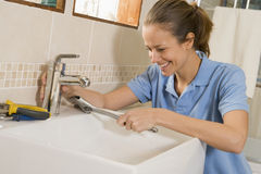 Plumber working on sink. Smiling Stock Photo