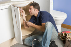 Plumber working on sink Royalty Free Stock Images