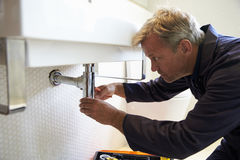Plumber Working On Sink In Bathroom Royalty Free Stock Photos