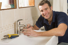 Plumber working on sink smiling Royalty Free Stock Photos