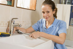 Plumber working on sink smiling Stock Photography