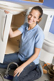 Plumber working on sink smiling. At camera Royalty Free Stock Photo