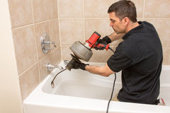 Plumber Working. Plumber unclogging a tub drain with an electric auger Royalty Free Stock Photos