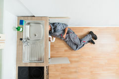 Plumber Working Under Kitchen Sink Stock Images