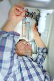 Plumber working under sink royalty free stock image