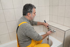 Plumber works in a bathroom bath toob faucet fixing Royalty Free Stock Photo