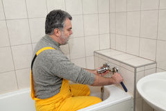 Plumber works in a bathroom bath toob faucet fixing Royalty Free Stock Photography