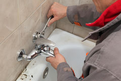 Plumber works in a bathroom Stock Photos