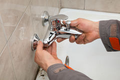 Plumber works in a bathroom Stock Images