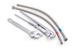 Plumber wrench, adjustable wrench and two hoses with braiding. Plumber wrench, adjustable wrench and two hoses in metallic braiding with connecting couplings on Royalty Free Stock Photo