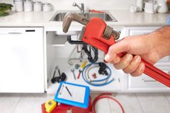 Plumber with wrench. Plumber handyman doing renovation in kitchen home royalty free stock photos