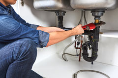 Plumber with wrench. Professional plumber doing renovation in kitchen home stock photography