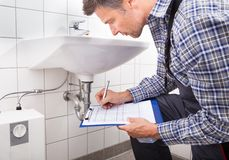 Plumber writing on clipboard Royalty Free Stock Image
