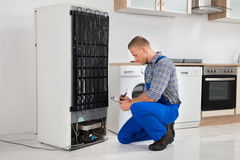 Plumber Writing On Clipboard In Front Of Refrigerator Royalty Free Stock Images