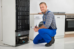 Plumber Writing On Clipboard In Front Of Refrigerator Stock Photography