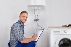 Plumber Writing Meter Reading On Clipboard Stock Photos