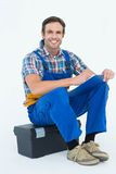 Plumber writing notes while sitting on tool box. Portrait of happy plumber writing notes while sitting on tool box over white background royalty free stock photos