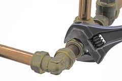 Plumber& x27; llave ajustable de s que refuerza la fontanería de cobre Foto de archivo libre de regalías