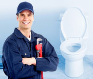 Plumber. Young plumber near a flush toilet Royalty Free Stock Photos