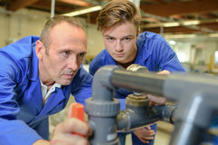 Plumbers checking on tubes Stock Photography