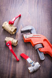 Plumbers fixtures and adjustable wrench on vintage Stock Image