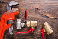Plumbers fixtures with red handles and monkey Royalty Free Stock Photography