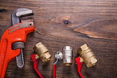 Plumbers fixtures with red handles and monkey Royalty Free Stock Image