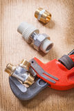 Plumbers pipe fixtures and wrench Stock Photography