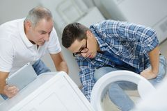 Plumbers repairing washing machine. Men royalty free stock image
