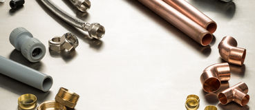 Plumbers Tools and Plumbing Materials Banner with Copy Space. Various plumbers tools and plumbing materials including copper pipe, elbow joint, wrench and stock image