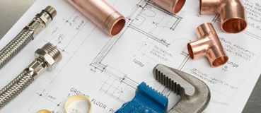 Plumbers Tools and Plumbing Materials Banner on House Plans. Various plumbers tools and plumbing materials including copper pipe, elbow joint, wrench and spanner Stock Photography