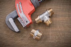 Plumbers wrench brass plumbing fixtures on cleaning mesh filter. Grid Stock Images